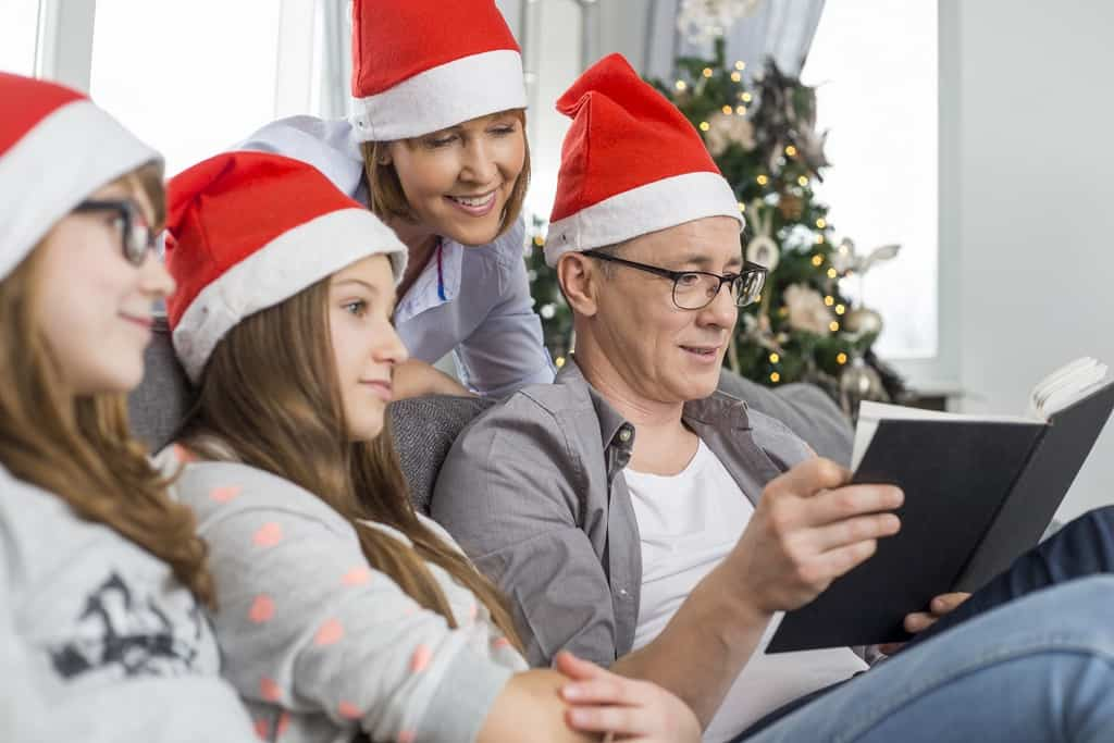 Father reading book for family at home during Christmas